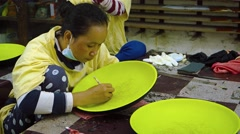 Local woman draws guide lines on a ceramic plate for a painting project Stock Footage
