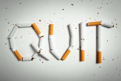 Broken cigarettes arranged as a word quit Stock Photos