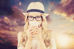 Composite image of gorgeous blonde hipster drinking out of take-away cup - stock photo