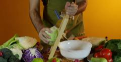 Man grating white cabbage with grater, close up, dolly shot on right. - stock footage