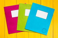 Exercise books on the yellow background - stock photo