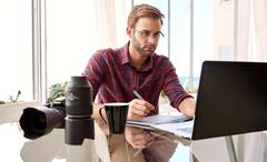 Amateur photographer working from his home studio - stock photo