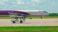 Crew directing a Cambodia Angkor Air plane at Don Mueang Airport - stock footage