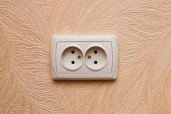 European electric outlet on wall covered with wallpaper Stock Photos