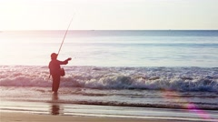 Local man fishing in the gentle surf on a beach in Phuket, Thailand Stock Footage
