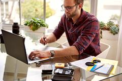 Young adult male entrepreneur creative sitting while working - stock photo