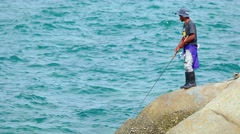Local man fishing with rod and reel from the rocks  in Phuket Thailand Stock Footage