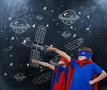Composite image of masked kids pretending to be superheroes Stock Photos