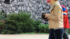 A Couple Russian Tourists is passing by the wall of artificial stalactite Stock Footage