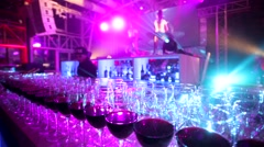 Steadycam walk in a nightclub, along a row of many glasses of red wine. Stock Footage