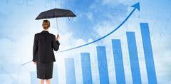 Composite image of businesswoman holding a black umbrella - stock photo
