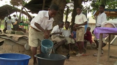 STUDENT FILLS  UP A BASIN WITH A BUCKET OF CLEAN WATER Stock Footage