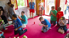 Buddhist worshippers kneel and pray before an alter at Wat Chalong - stock footage