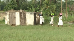FEMALE STUDENTS BRINGING WATER BASINS TO OUTDOOR TOILET Stock Footage