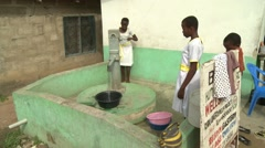 FEMALE STUDENTS PUMPING WATER FROM A WELL Stock Footage