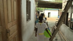 CAMERA FOLLOWS FEMALE STUDENTS CARRYING WATER TUBS AS THEY WALK TO A WELL - stock footage