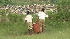 STUDENTS CARRYING FULL BIN TO TRASH HEAP Stock Footage