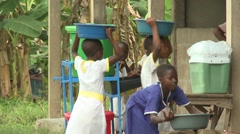 STUDENTS WITH WATER BASINS NEXT TO HANDWASHING STATION Stock Footage