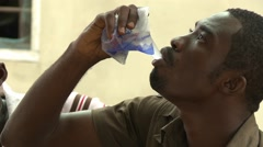 CLOSE UP: TEACHER DRINKING SACHET WATER AND HANDS ONE TO FELLOW TEACHER Stock Footage