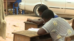 STUDENTS WRITING ON WOODEN DESKS IN OUTDOOR CLASSROOM Stock Footage