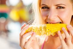 Woman in bikini eating corn. Summer and heat - stock photo