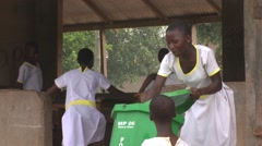 MED FEMALE STUDENT CLEANS THE GREEN BUCKET OF THE HANDWASHING STATION Stock Footage