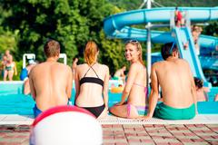 Two couples sunbathing at the swimming pool. Summer heat - stock photo