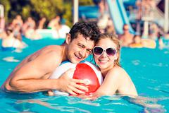 Couple with sunglasses in swimming pool. Summer and water - stock photo