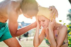 Man helping woman in bikini with heatstroke, summer heat - stock photo