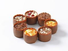 Delicate milk chocolate cups with liqueur and ganache centres - stock photo