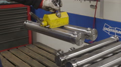Metal tubes being arranged using a magnet - stock footage