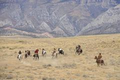 Cowboys herding horses in wilderness, Rocky Mountain, Wyoming, USA - stock photo