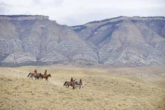 Cowboys and Cowgirls riding horse in wilderness, Rocky Mountains, Wyoming, USA - stock photo