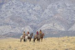 Cowboys and Cowgirls riding horses in wlderness, Rocky Mountains,Wyoming, USA - stock photo