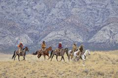 Stock Photo of Cowboys and Cowgirls riding horses in wilderness, Rocky Mountains, Wyoming, USA