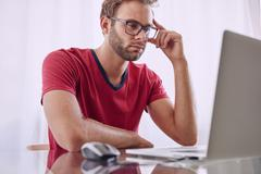 Man deep in concentration infront of computer - stock photo