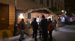 Group of people standing in front of a street stall on Christmas in Budapest Stock Footage