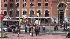 4K Heavy traffic street people cross large avenue arena building Barcelona city  Stock Footage