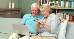 Senior couple using laptop and holding credit card Arkistovideo