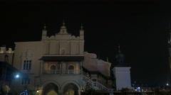 Walking next to the Sukiennice Palace in Rynek Glowny square, Krakow, at night Stock Footage