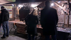 Admiring the products at a blacksmith's shop at the Christmas market in Krakow Stock Footage