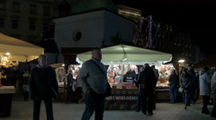 Stalls near the St. Wojciech Church at the Christmas market in Krakow, at night - stock footage