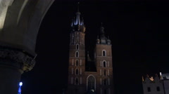 Towers of St. Mary's Basilica seen from Rynek Glowny square in Krakow, at night Stock Footage