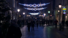 Walking and riding bikes on Grodzka street on Christmas in Krakow, at night Stock Footage