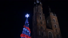 Low angle view of Saint Mary Basilica and a Christmas tree in Krakow, at night - stock footage