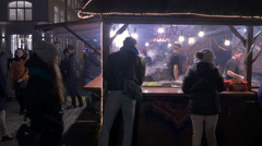 People buying sausages from a meat stall at the Christmas market in Krakow Stock Footage