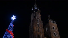 Saint Mary Basilica tower and a Christmas tree at the Christmas market in Krakow Stock Footage