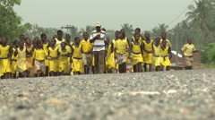 LOW ANGLE - A BIG GROUP OF STUDENTS WALK UP THE ROAD Stock Footage