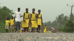 LOW ANGLE STUDENTS WALK DOWN THE ROAD CARRYING BROOMS AND MACHETES Stock Footage