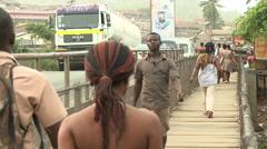 PEDESTRIANS WALK ACROSS BRIDGE OVER DENSU RIVER Stock Footage